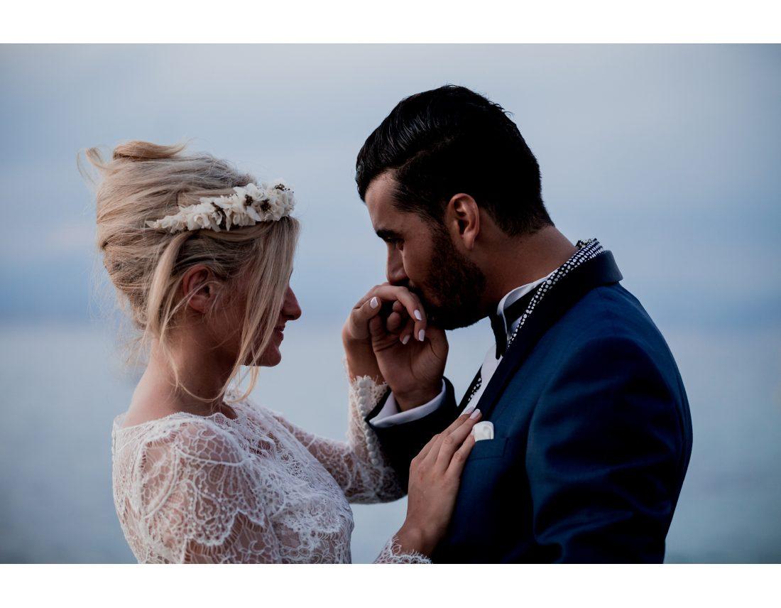 Marié embrasant la main de sa femme devant la mer.