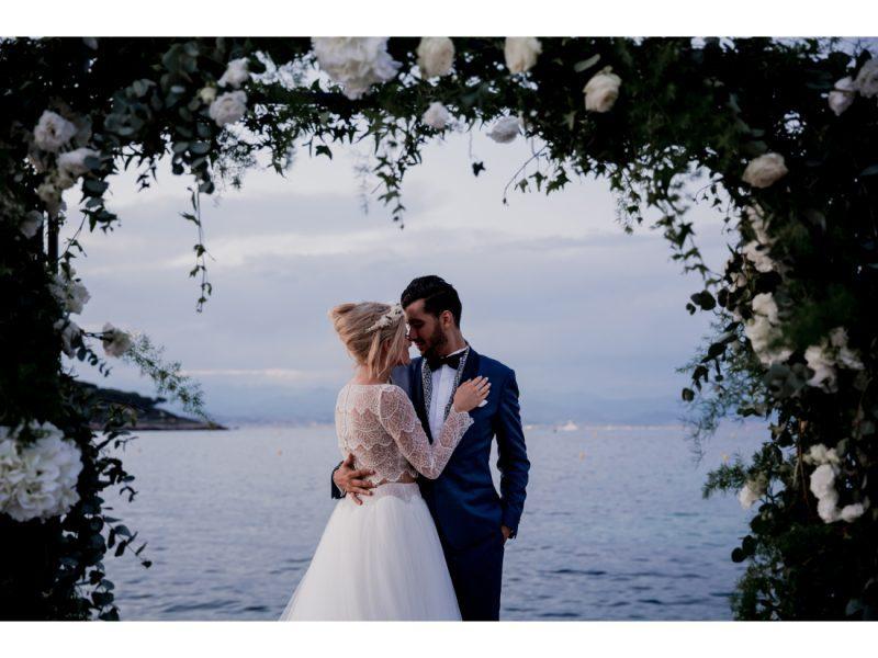 Couple de mariée devant la mer, arche de fleur.