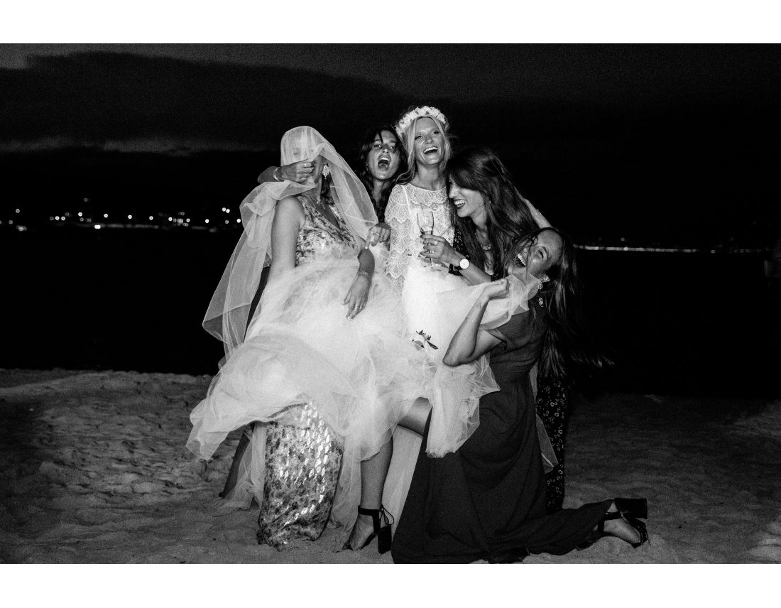 Groupe de copines rigolant avec la robe de la mariée.