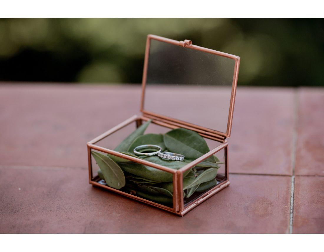 Détails des alliances sur lit de feuilles d'olivier dans boite en verre.